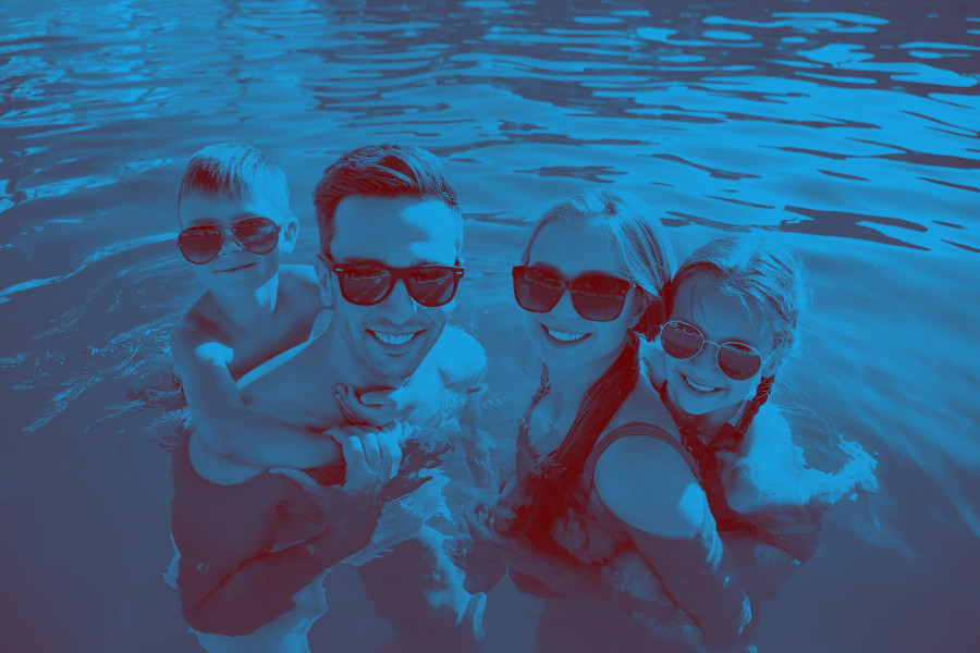Happy family in swimming pool on summer day